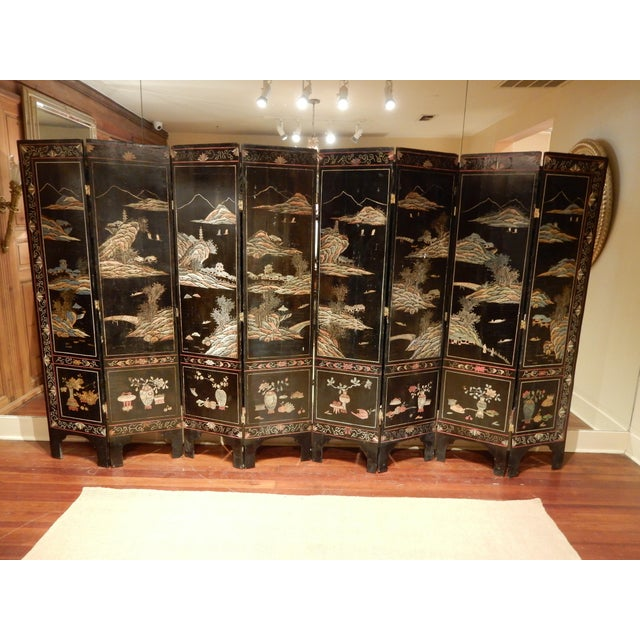 19th-century black lacquered 8 panel Coromandel screen. Faded soft tones of color added to its patina. The screen is...
