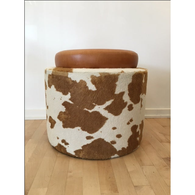 Custom brown and white hair-on-hide ottoman with brown leather seat. This would be the perfect footstool or seat if you...