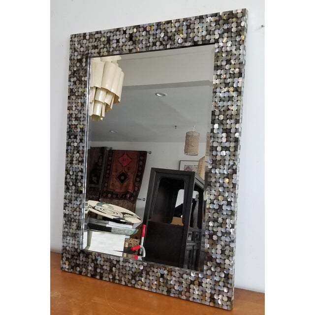 Elegant silver mother-of-pearl shell has been used to create an iridescent element in architecture. Cut-cornered square...
