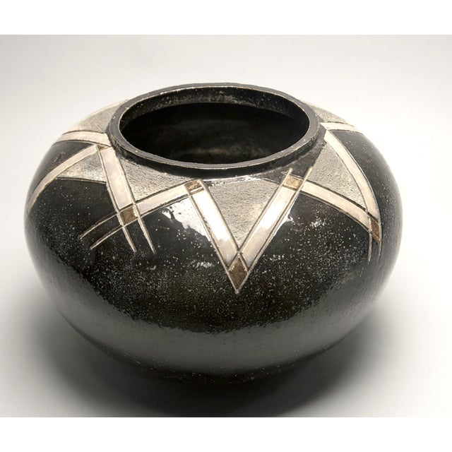 Mid Century hand thrown ceramic pot with low, round form, black glaze and incised deco style decoration around neck with...