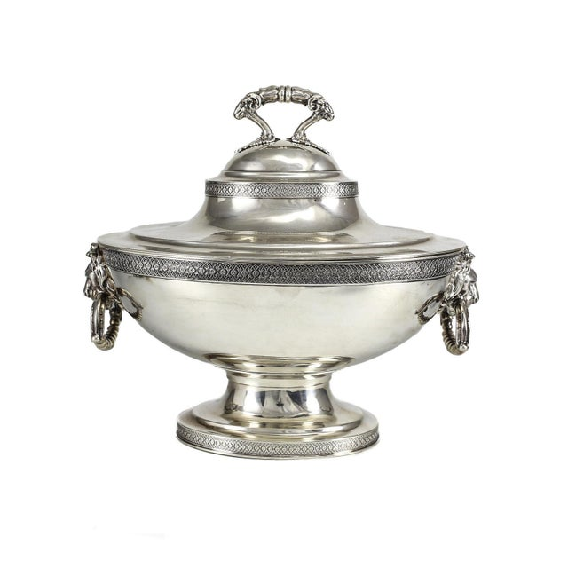 An attractive American sterling silver soup tureen with cover. The ends fashioned with lion heads, their mouths holding...