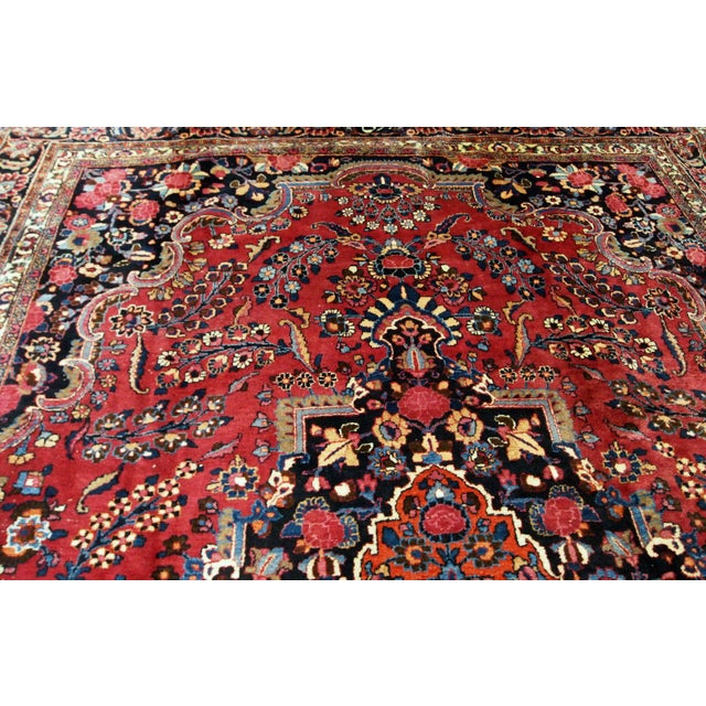 Hand made antique Persian Mashad rug in good condition. This rug is in deep red shade with orange medallion and navy blue...
