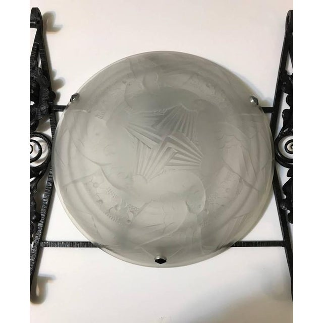 Stunning French Art Deco single sconce. With clear frosted glass shade having intricate geometric and birds in flight...