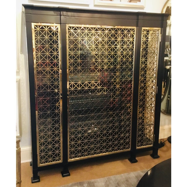 Original Retail $19,700, stylish Caracole modern black and gold display cabinet, black finished wood cabinet with gold...