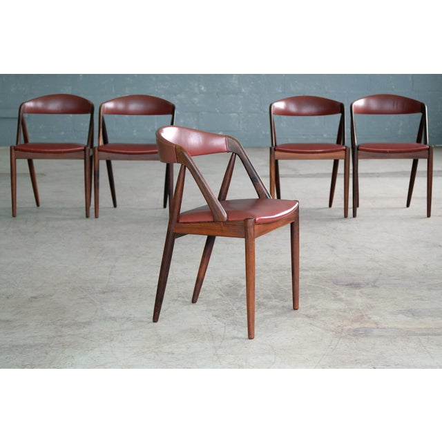 This set of iconic dining room chairs known as Model 31 were designed by Kai Kristiansen in 1956 and manufactured by Schou...