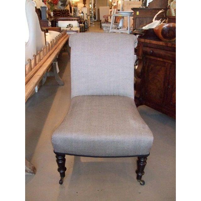 Napoleon III slipper chair with ebonized turned legs newly upholstered in a herringbone black and white fabric.