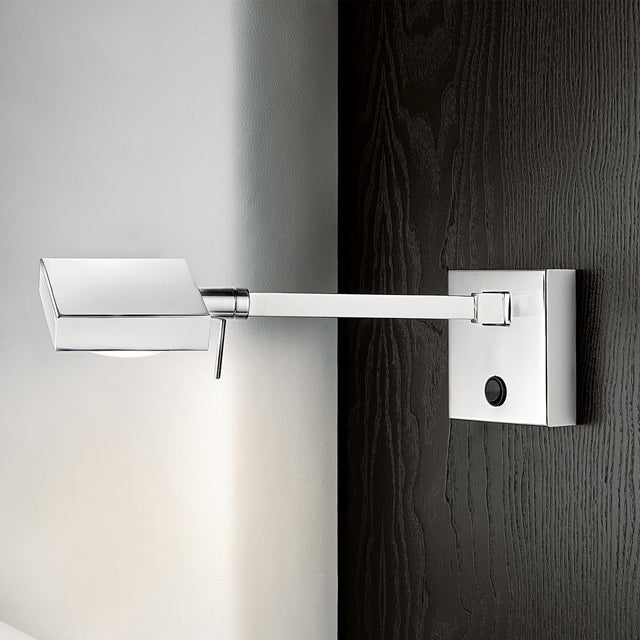 A polished chrome contemporary style wall light with an adjustable swivelling head and arm that moves left-right....