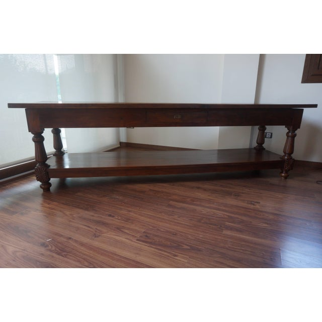 19th century refectory walnut farm table. This solid and utilitarian table is raised on four topie shaped feet with full...