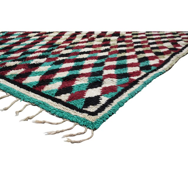 Hand-knotted Moroccan rug with low wool pile. Lively and complex Berber pattern throughout in maroon and teal gradation....