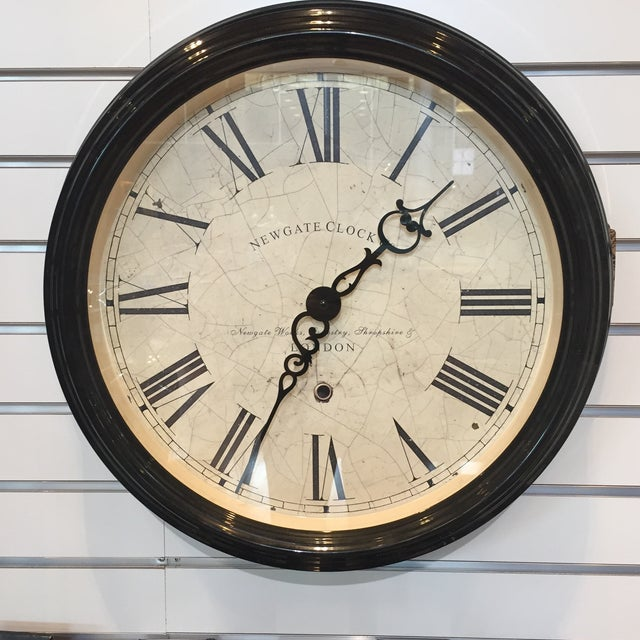 This is a Newgate Clock Co of London wall clock. The piece includes a cream/beige colored face with Roman numerals. Depth...
