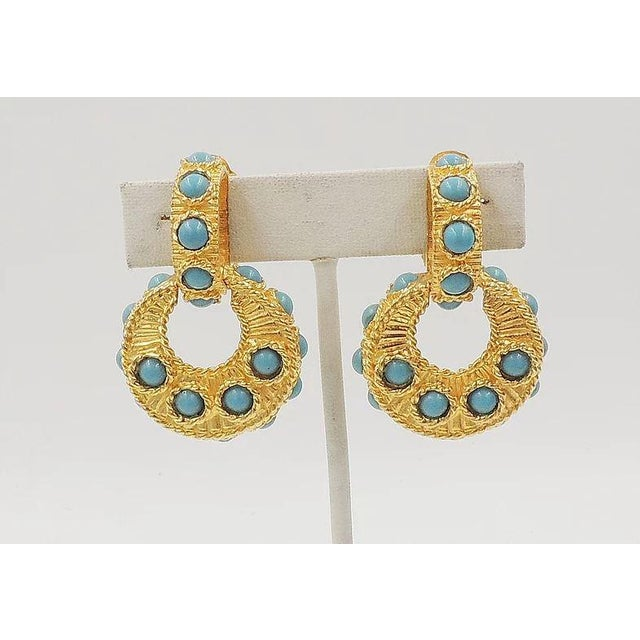 """1960s goldtone and cabochon faux-turquoise rhinestone hoop clip back earrings. Marked """"Mimi di N."""" Measure: 1 3/4 inches..."""