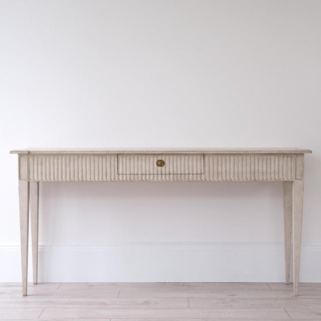 A very fine bespoke hand carved Gustavian console table featuring a shaped top with single fluted drawer below, matching...
