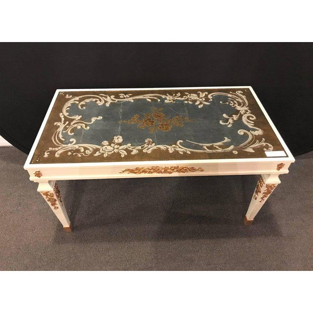 A Hollywood Regency églomisé top parcel paint and gilt decorated coffee table with a carved base.