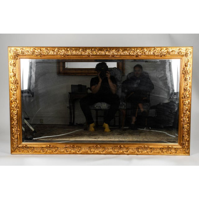 Large vintage Italian gilded wood framed hanging bevelled wall mirror. The mirror is in excellent vintage condition. The...