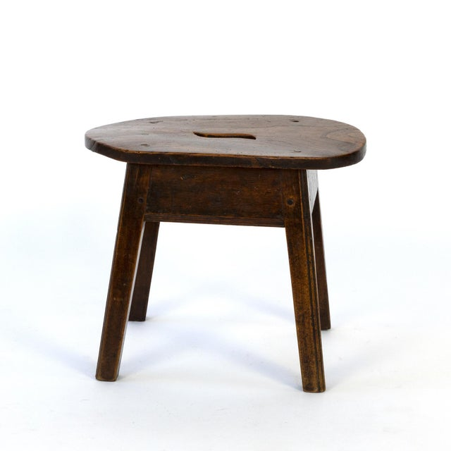 Rustic oval elmwood work stool with a pierced top and four legs, English, Circa 1830. height: 12 in. 30.5 cm., width: 17...
