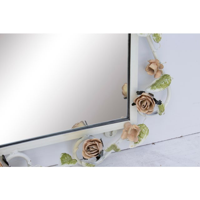 Romantic Italian tole mirror with pale pink roses and light green leaves winding around its border. Mirror can be hung...