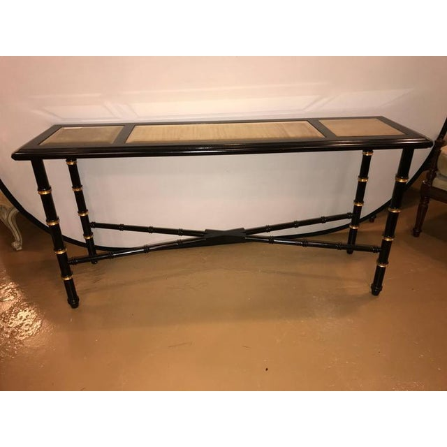 An ebonized faux bamboo and gilt gold console or serving table. The group of three gilt gold glass panels framed with...