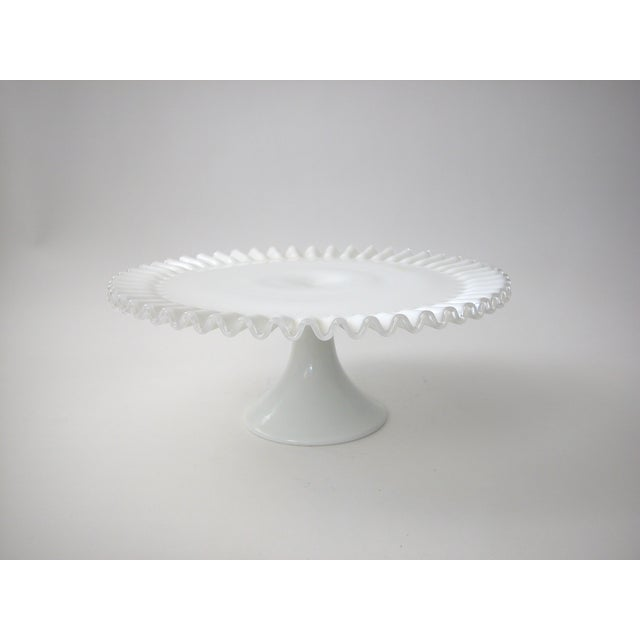 Vintage Fenton Cake Stand. Milk glass pedestal stand with a ruffled edged in clear glass.
