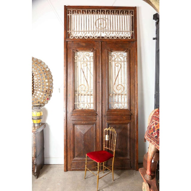 Large French painted double entry doors with transom frame. Wrought Iron work insert in door frame and top. Nice high...