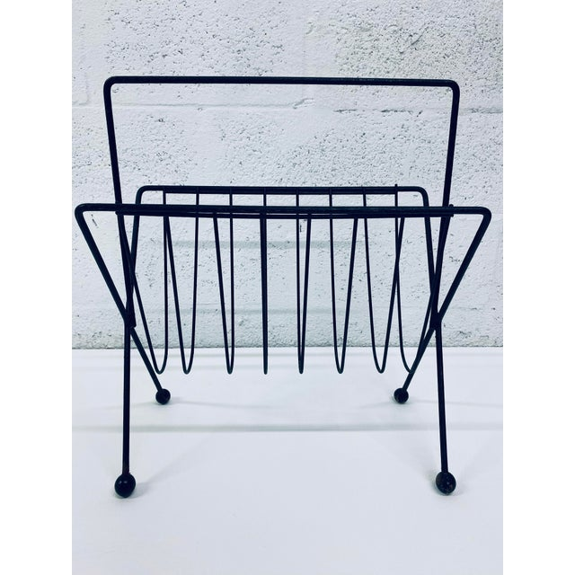 Tony Paul steel wire magazine rack with ball feet and handle. Maintains original black lacquer finish which shows signs or...