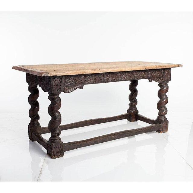 Library table with a rustic, weather-worn top and intricate apron carvings. Barley twist legs give it true character.