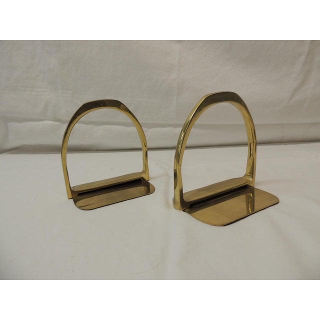 Pair of brass Hermès style horse saddle stirrups bookends Polished brass finish Size: 5 x 5.5 x 3.5.