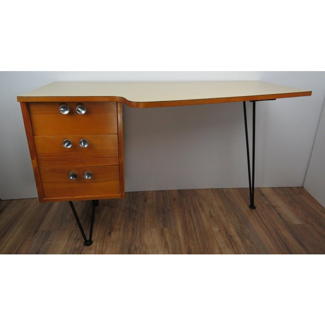 Striking 1950's light walnut writing desk manufactured by Mengel Furniture Company. Freeform Formica top with black iron...