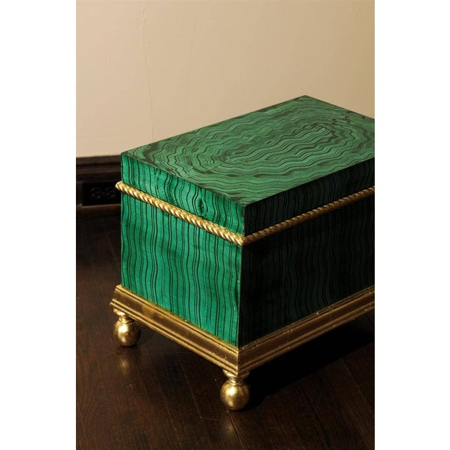 Hollywood Regency wooden chest or trunk hand-painted in a faux malachite design with gold leaf piping beneath a removable...