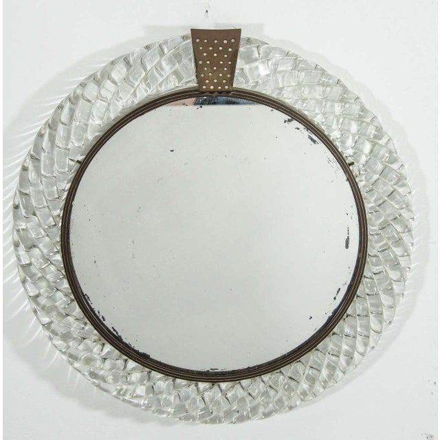 An Italian Murano clear art glass 'treccia' ('braid') framed round wall mirror with bronze decorative accent, circa Early...
