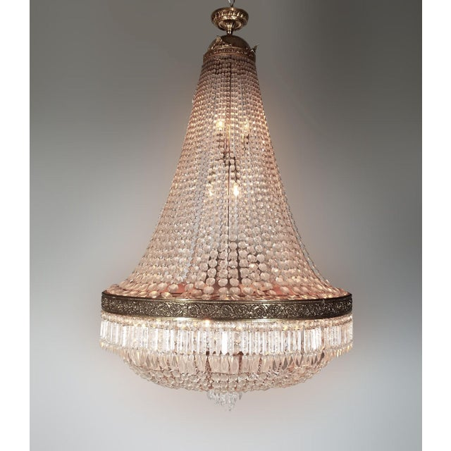 Phenomenal Empire style 5 foot tall 22 light crystal chandelier features a brass crown and a bronze strip around the...