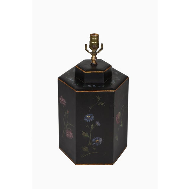 This canister style tea caddy lamp is decorated with painted golden flora and featuring blue, white, and red flowers