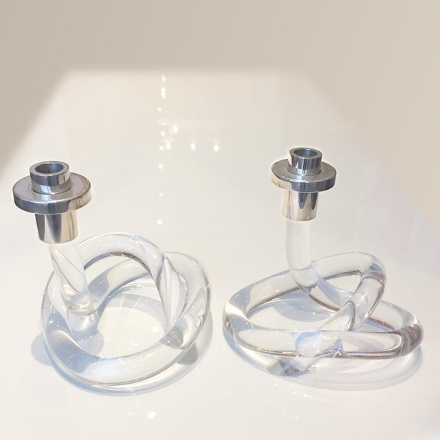 Two 1960's candlesticks attributed to designer Dorothy Thorpe in lucite. There is some minor cracking to the bases, in a...