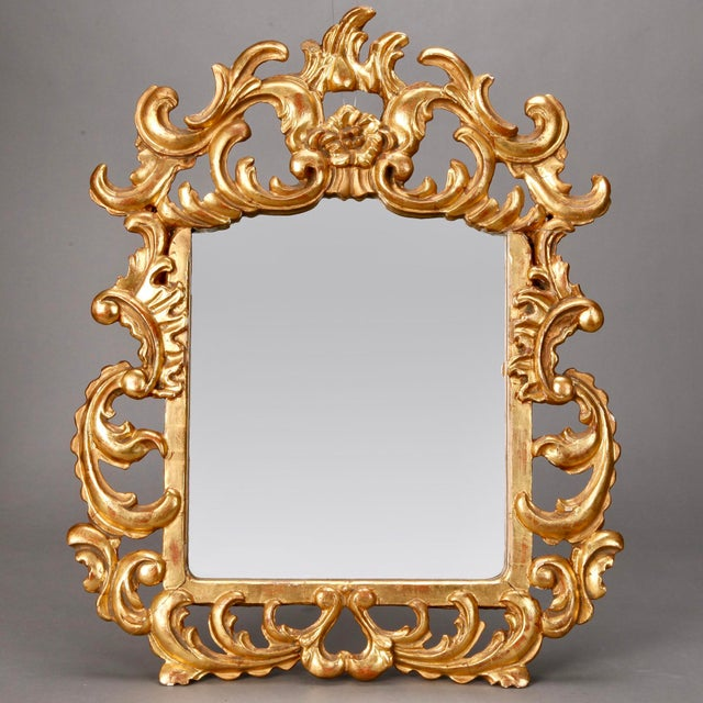Circa 1900 Italian gilded mirror with elaborate open work scrolled frame and crest. Excellent antique condition.