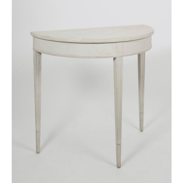 A vintage Gustavian style small demi lune table, in a painted white distressed finish. The surface patina shows expected...