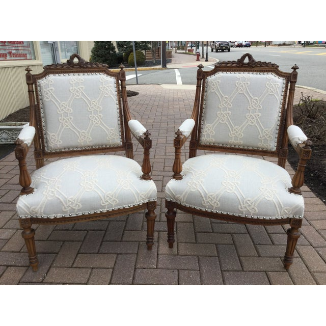 A pair of antique 19th century French walnut chairs with delicately carved frames. These chairs have been re-upholstered...