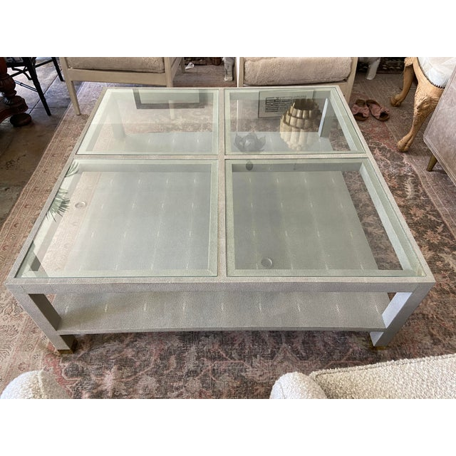 Generously sized faux shagreen coffee or cocktail table in sandy taupe shade. Glass top is comprised of four large inset...