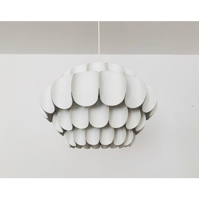 Wonderful white metal pendant lamp by Thorsten Orrling from the 1960s. The extraordinary design creates a fantastic play...