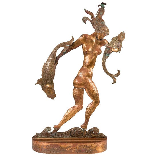 An Art Deco hammered copper sculpture of a nude woman wading through water and carrying two fish.