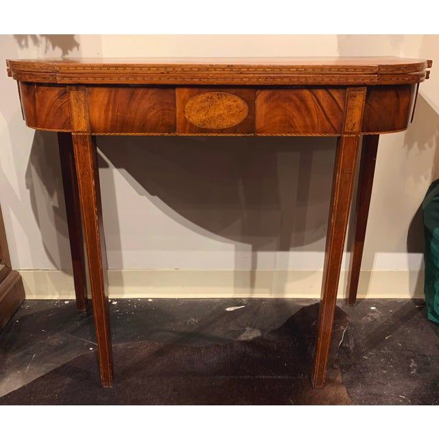 George III Mahogany and Inlaid Fold-Top Table. This table features a shaped rectangular top opening to a square top with...