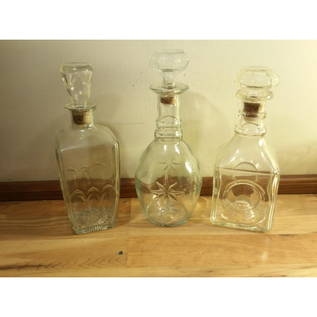 Three vintage whiskey decanters square, round, and rectangle in shape. The round decanter with stars has a greenish tint/...
