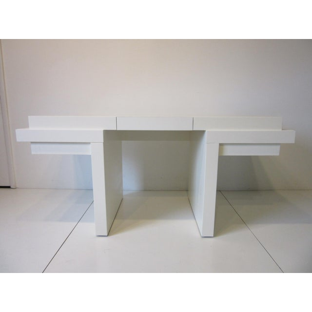 A very well crafted cream lacquer sculptural desk with three drawers and mulit level desk top design having a curved front...