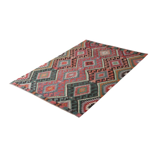 Handwoven in a wool flatweave originating from Turkey circa 1950-1960, this vintage Kilim rug connotes a mid-century...
