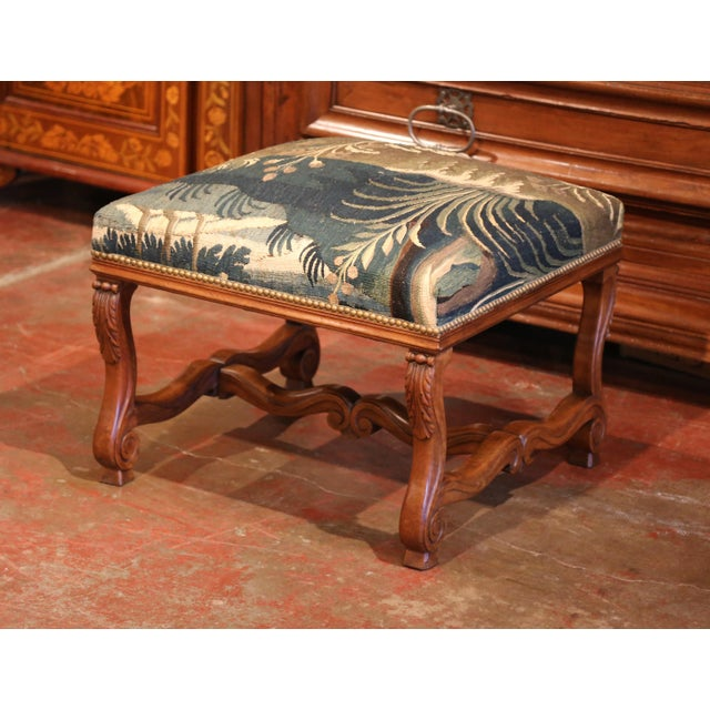 This elegant antique fruitwood stool was crafted in Southern France, circa 1880. The square seat features four scrolled...