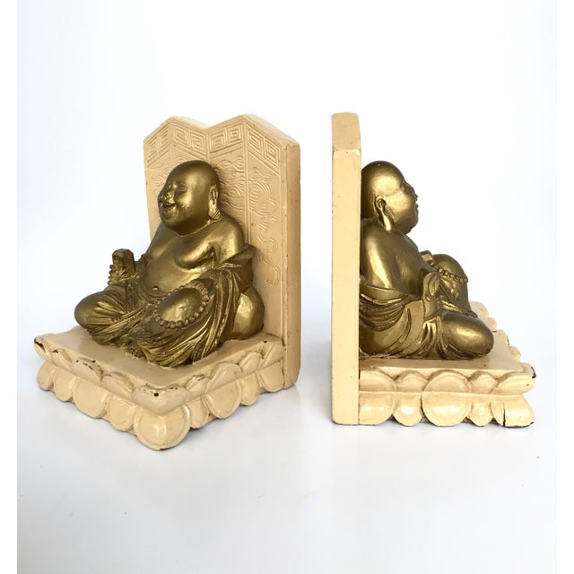 Vintage Asian Bookends with Smiling Buddha seated. Structure is made of wood painted in beige and Statuette is made of...