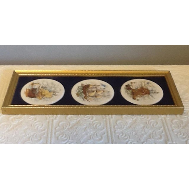 Each of the 3 miniature ceramic round plates/coasters mounted on rich navy velvet witihin a single frame feature a...