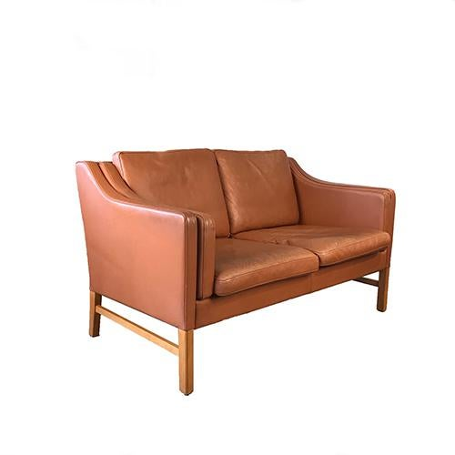 Beautiful butterscotch leather two seat sofa set on four light stained wooden legs. Features two loose back cushions, two...