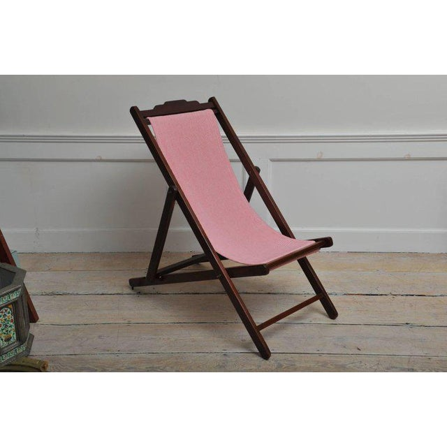 A folding and adjustable (three settings) teak lounge chair from the 1940s with a red and white striped sling seat. The...