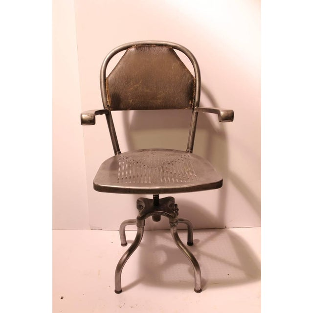 """1930's American industrial metal desk chair with a leather back. Adjustable height 17""""-21"""""""