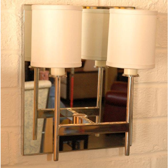 Two-Arm Mirror Back Sconce by Paul Marra. Steel frame with inset clear mirror. Shown in polished nickel. Price quoted is...