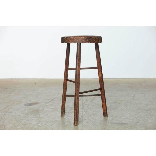 Minimalist rustic three legged stool with massive wood top.